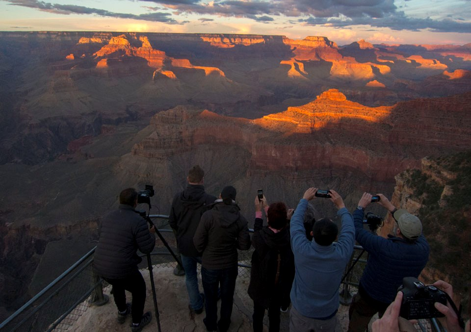 A group of visitors stand facing a sunset-lit canyon, photographing it with smart phones and traditional cameras.