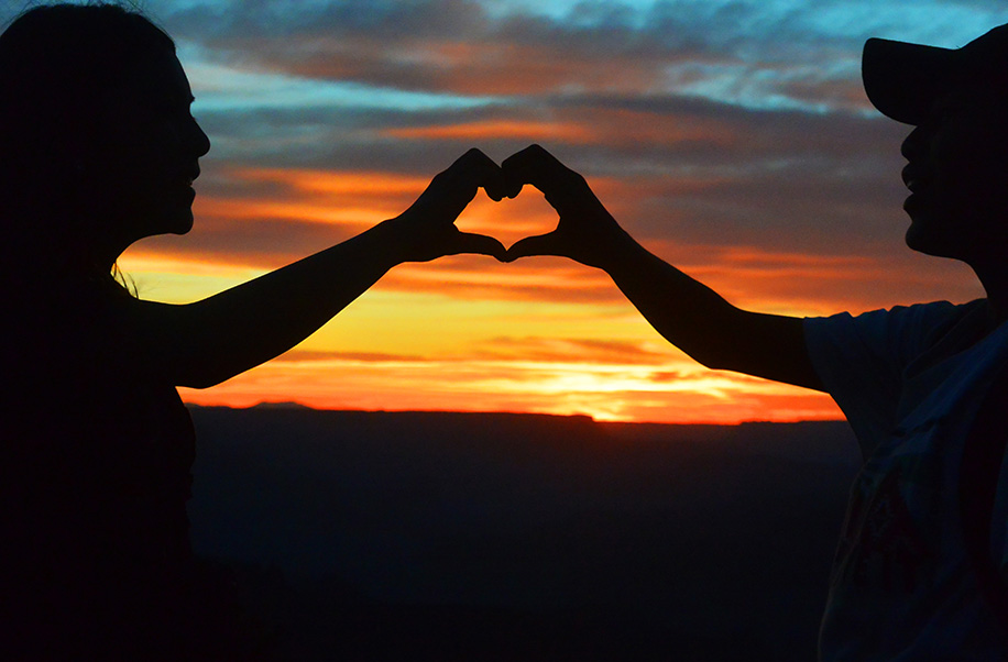Youth make a heart shape with their hands in front of a sunset.