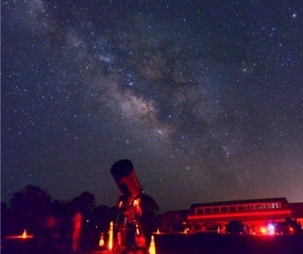 Red lights illuminate telescopes pointed at the night sky and milky way overhead.