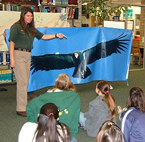 Students sitting on the floor listening to a female guest speaker who is standing to the left of a life-size banner of a California condor in flight.