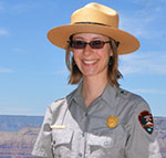 Smiling female ranger standing in front of Grand Canyon