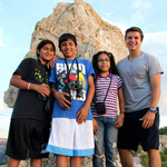 Four teens wearing summer clothes pose in front of a pointed limestone slab. Photo courtesy parks in focus.