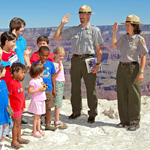 Eight kids being sworn in as Junior Rangers by two park rangers standing on their right.