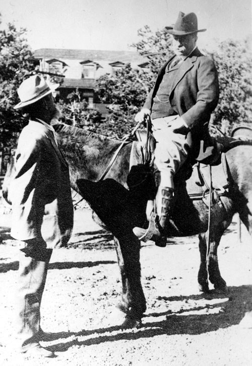 Teddy Roosevelt, mounted on a horse, speaking to John Hance