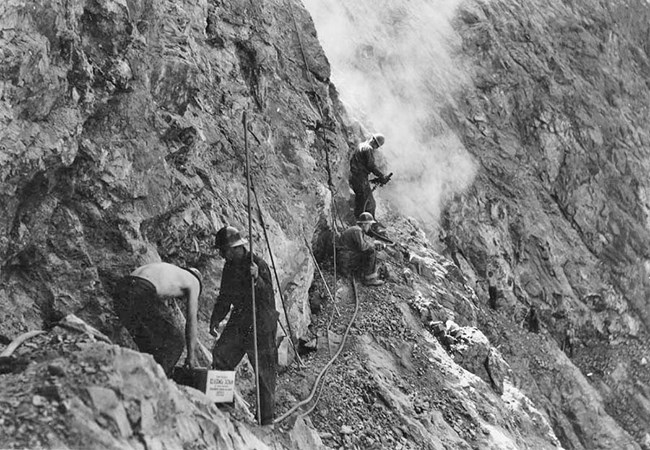 Three workers carving the cliff into a trail