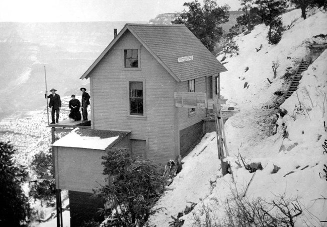 Historic Kolb Studio: a smaller building pale in color built into the side of a snowy cliff. Three people dressed in dark colors stand on a porch.