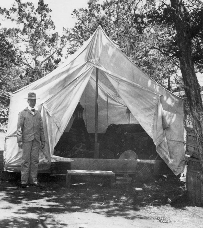 Early entrepeneur in front of large white tent in the woods