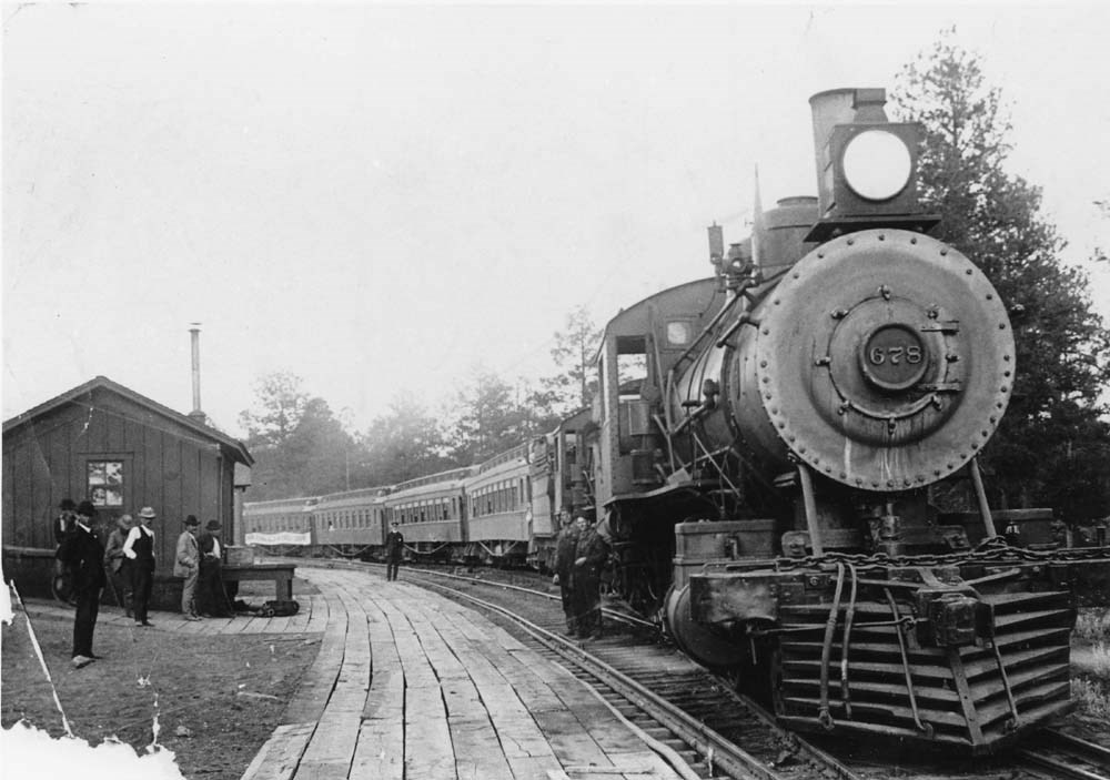 A steam engine pulls forward next to a wooden walkway with a small wood building. Pine trees are in the background.