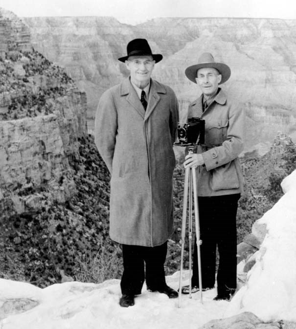 Two brothers holding a tripod stand in front of the snowy canyon