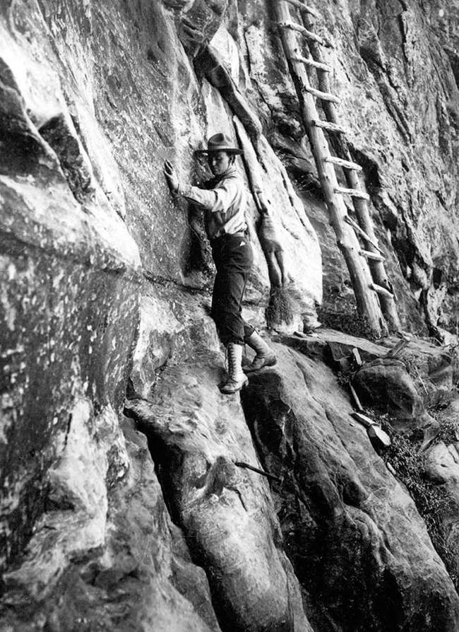 Kolb traversing a vertical cliff face with a ladder close by