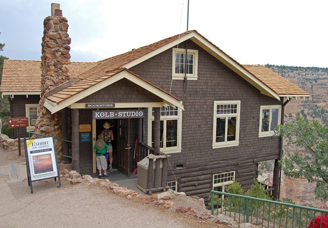 "Dark brown house with white trim built into the edge of a cliff, with Grand Canyon in the background. A sign above the door reads ""Kolb Studio"""