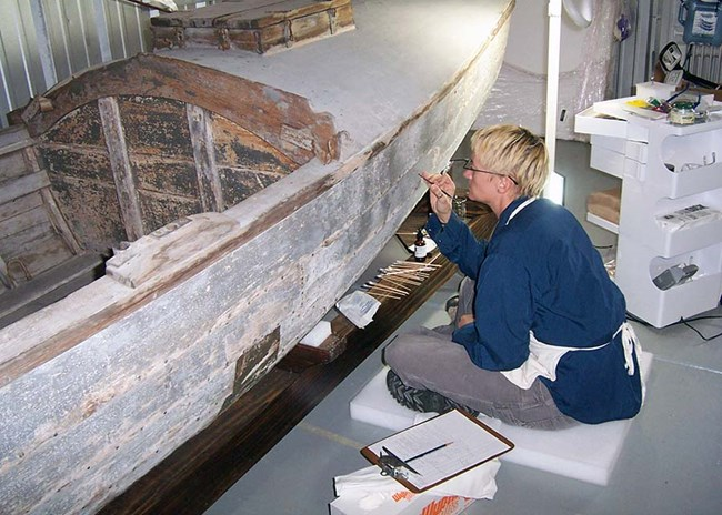 Touching up the white paint-job on a wooden boat
