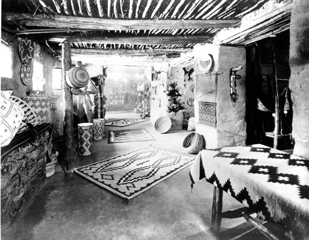 A black and white photo of a sales room with baskets and Navajo rugs.