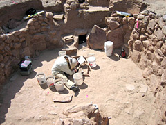 Archeologist uncovering a kiva.