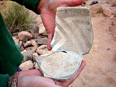 Archeologist fitting pieces broken pot together.