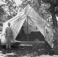 man standing next to canvas tent
