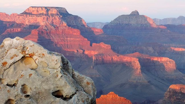 Grand Canyon rock formations turned pink and blue by the sunset.