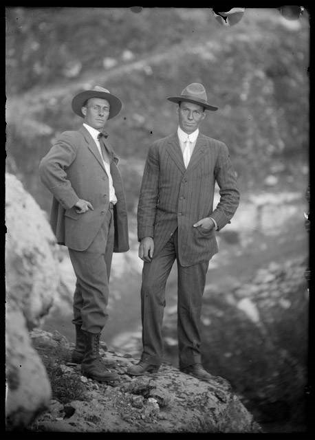 Kolb brothers dressed in coats and hats, standing on a rock in front of Grand Canyon.