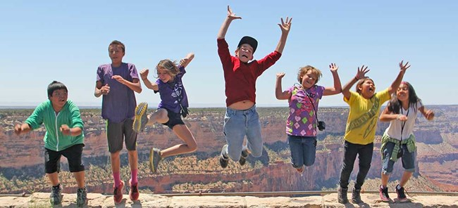Seven youth jumping up in the air with Grand Canyon as a background behind them