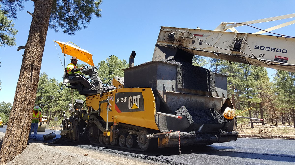 a large, yellow paving machine is spreading asphalt as it slowly moves down a highway. A Large white conveyor arm is transferring asphalt from another vehicle to the paving machine.