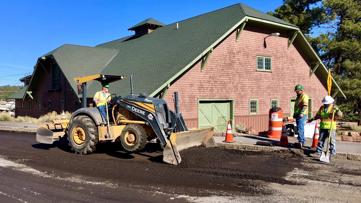 Three men wearing hard hats and safety vests work with a piece of heavy equipment to smooth asphalt; brown barn in background