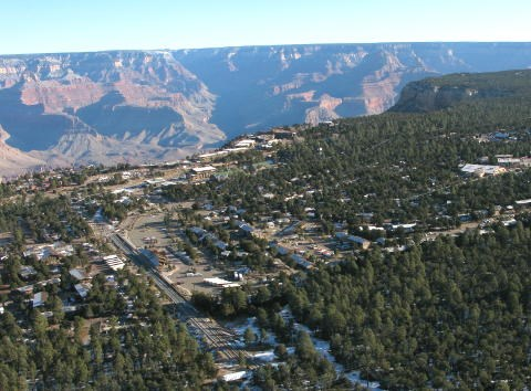 Aerial view of village roads, houses and buildings in a forested area on the edge vast canyon landscape of peaks and cliffs.