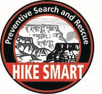 a black circle with a black line drawing of Grand Canyon inside. a banner across the front of the logo reads Hike Smart in white letters on a red background