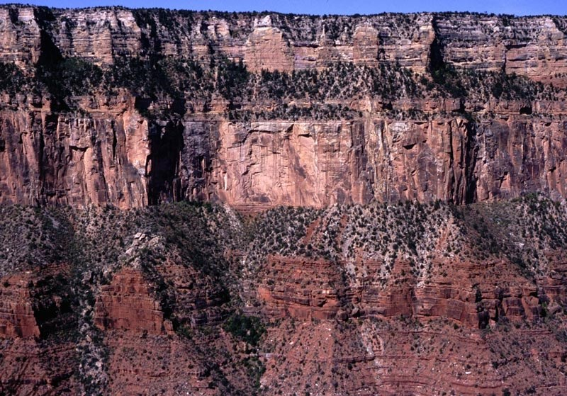 Vertical canyon cliffs showing striations of different colored rock.