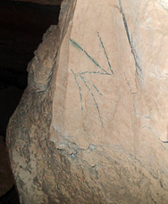 arrow shape engraving scratched in cave wall.