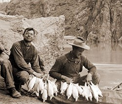 15774 - 2 MEN WITH A STRING OF HUMPBACK CHUB FISH & COLLAPSIBLE BOAT. COLORADO RIVER NEAR PHANTOM RANCH. CIRCA 1911. RUST COLLECTION