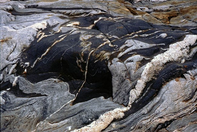 Igneous rock showing waves of gray and black.