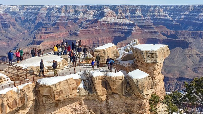 a scenic overlook on top of a large rock outcropping. Snow covers the ground. Small groups of people are behind metal guardrails and viewing a vast canyon landscape of colorful peaks and cliffs.