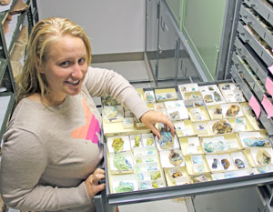 Geologist-in-Park Janelle Rohweller standing by mineral specimens.