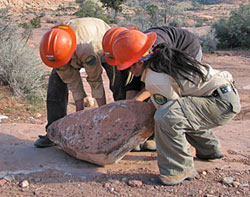 CREC crew of three moving a large slab of rock.
