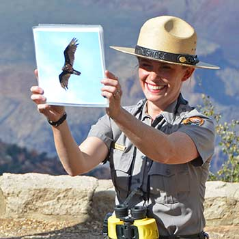 Park ranger on the canyon rim conducting a condor program and holding up a photo of a condor in flight.