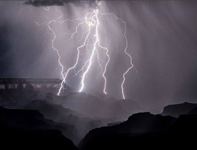 Multiple bolts of lightning illuminating the night and striking several nearby buttes within a canyon landscape of cliffs and peaks. Photo courtesy Daniel Pawlak
