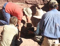 Four archeologists examine a prehistoric pot.