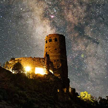 Milky Way in the sky over the Desert View Watchtower. Bright light is outlining the lower-story windows in the foreground, but the dozen or so windows in the tower on the left are dark.