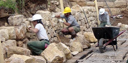 3 masons reconstructing historic wall.