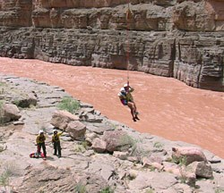 A rafter who had been stranded by flood waters on a ledge above Havasu Creek is lowered to the shore of the Colorado River.