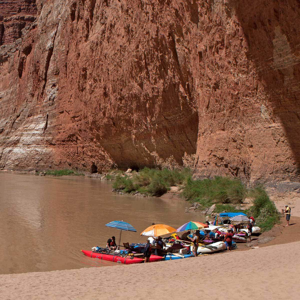 A group of rafters beneath colorful umbrellas rest at the shore next to a large cliff.