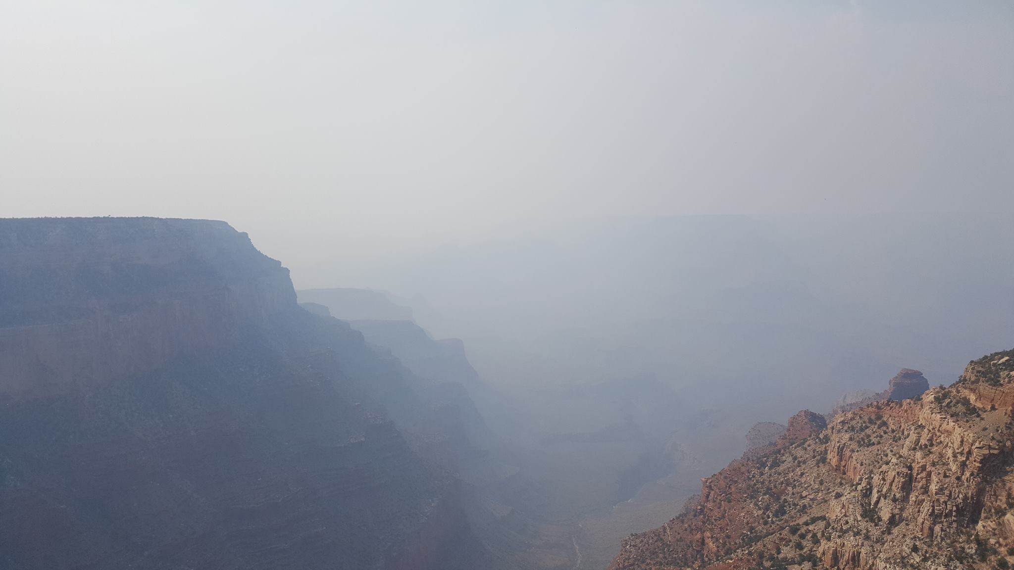 View from the rim of a canyon, past nearby cliffs into a smoke-filled interior