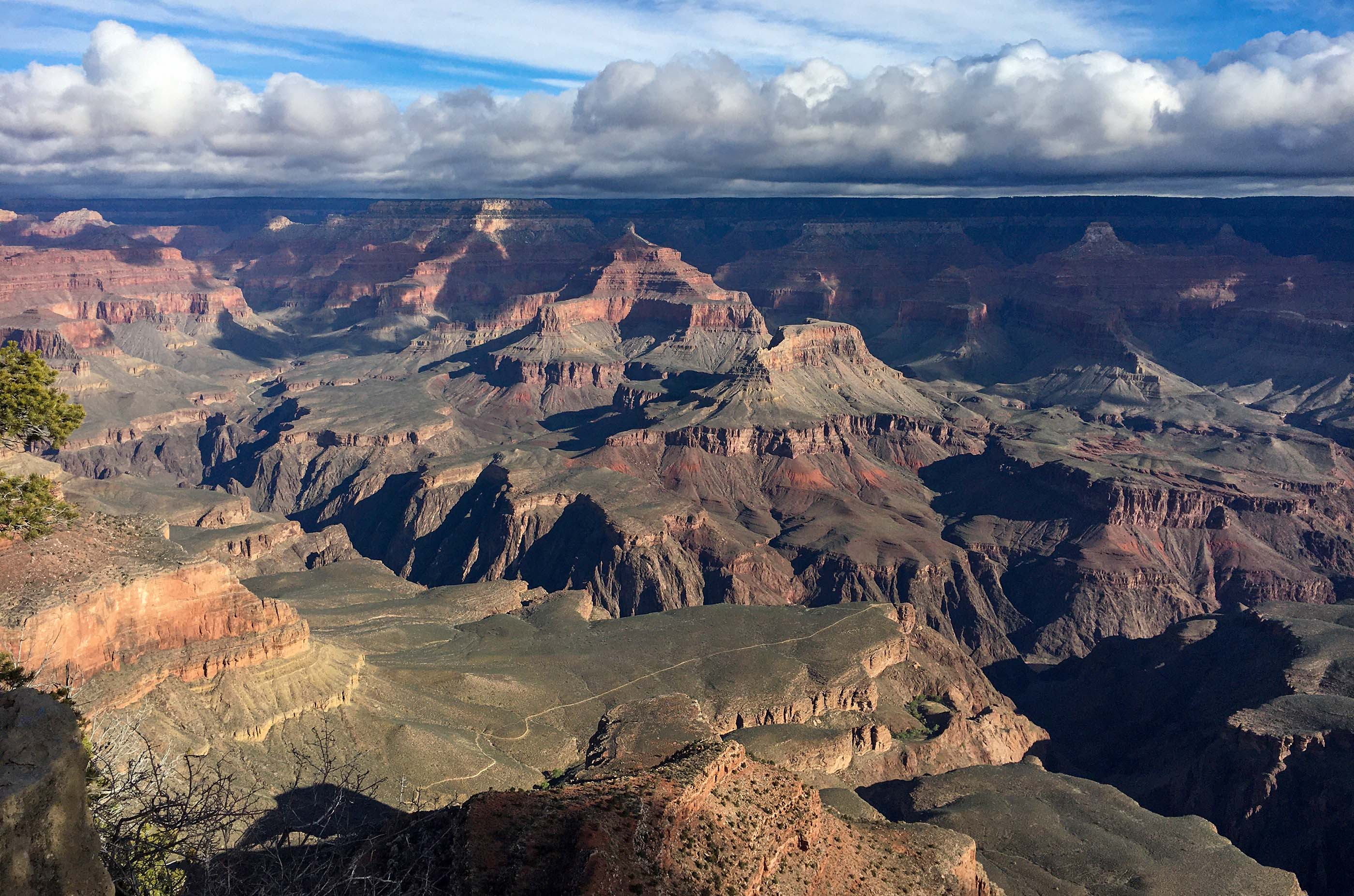 looking down across a plateau within a vast canyon with colorful peaks rising thousands of feet above. Threatening storm clouds shadow the distant rim.