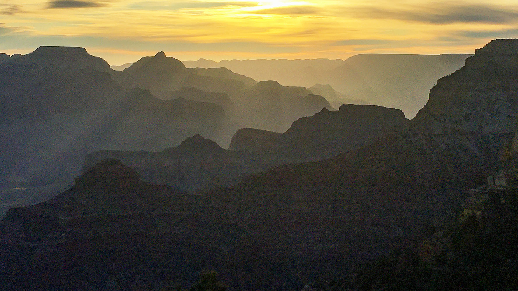 a series of silhouetted ridgelines and promontories bathed in yellow sunrise light.