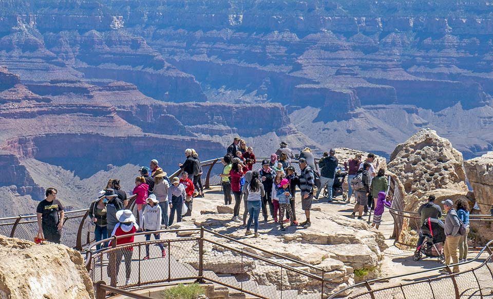 Behind metal railings at a scenic overlook, several dozen sightseers are viewing a canyon landscape