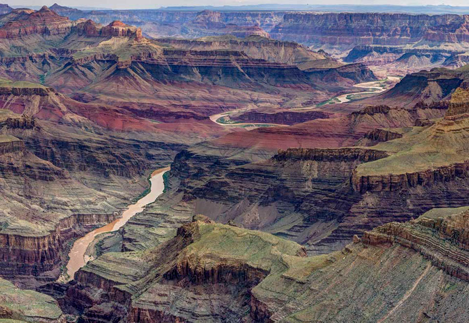 A muddy river meandering through a complex desert landscape of stratified cliffs and ridgelines.