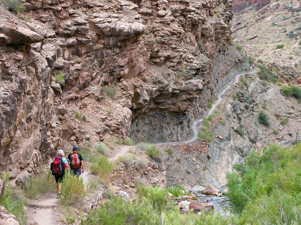 Two hikers descend down the North Kaibab Trail along Bright Angel Creek