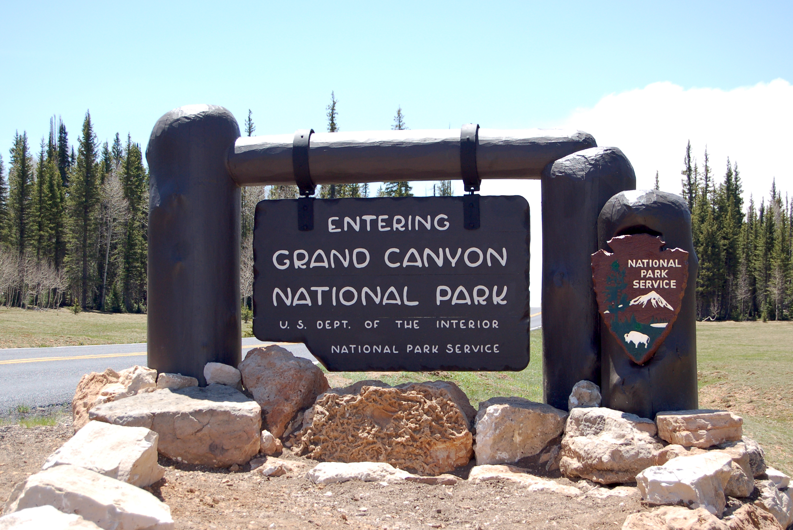 dark brown wooden Grand Canyon National Park entrance sign in a meadow