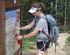 hiker wearing a gray t-shirt and a white visor fills up a water bottle at the North Kaibab trailhead.
