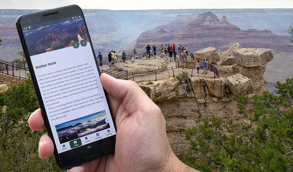 hand holding cellular phone that displays photos and text for a location. In the background, people at a scenic overlook with peak visible in the distance.